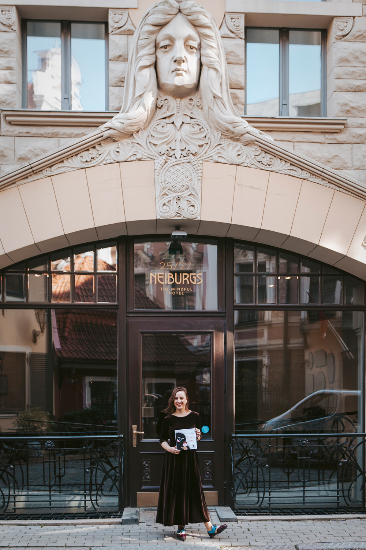 Zane Zusta at the Art Nouveau facade of the Riga hotel Neiburgs