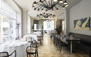 Gaišs art nouveau stilā ieturēts restorāns ar parketa grīdām, Thonet mēbelēm, MOOOI Dear Ingo griestu lampām