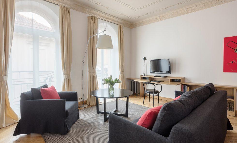 Plaša dzīvojamā telpa ar dizaina mēbelēm un lampām, iebūvētu virtuvi, balkoniem