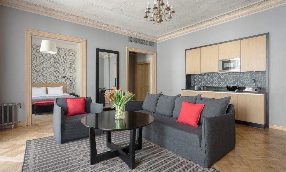 Dzīvojamā istabā dīvāns un atpūtas krēsli, griesti ar greznu dekoru, liels spogulis, iebūvēta virtuve