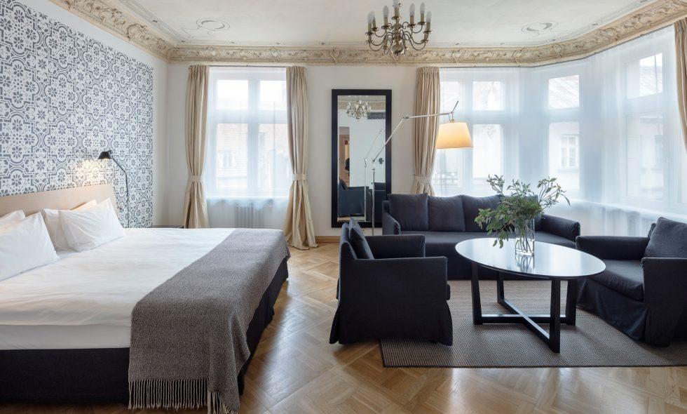 Plaša un gaiša telpa ar lielu stūra logu, grezni griestu rotājumi, dizaina mēbeles un dabīga zīda aizkari