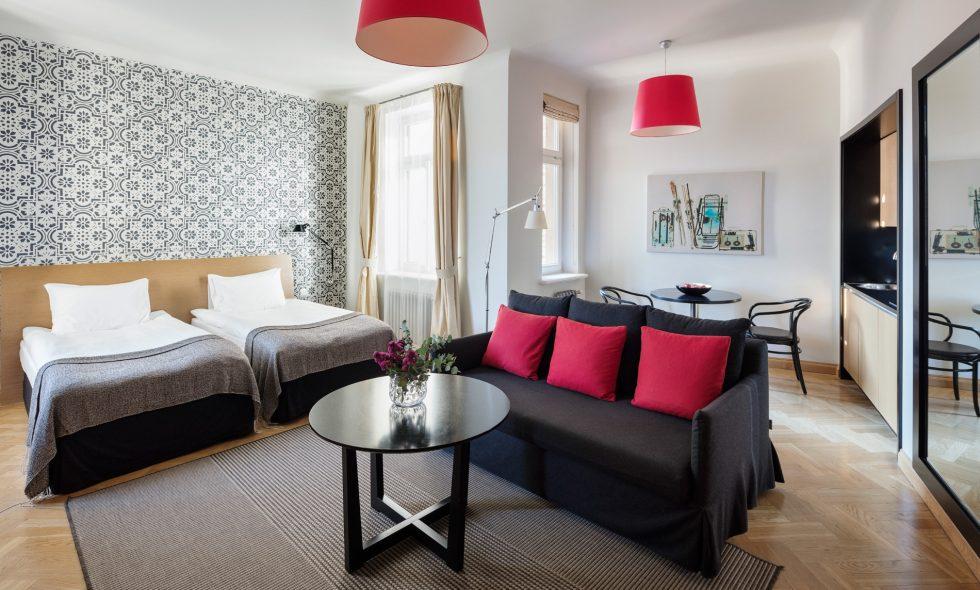 Gaišs apartaments ar atpūtas zonu, ērtu darba vietu, dizaina lampām, parketa grīdu un divām atsevišķām gultām