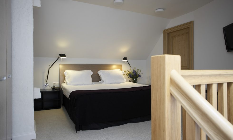 On the second floor, comfortable bedroom with spacious en-suite bathroom. Artemide designer lamps