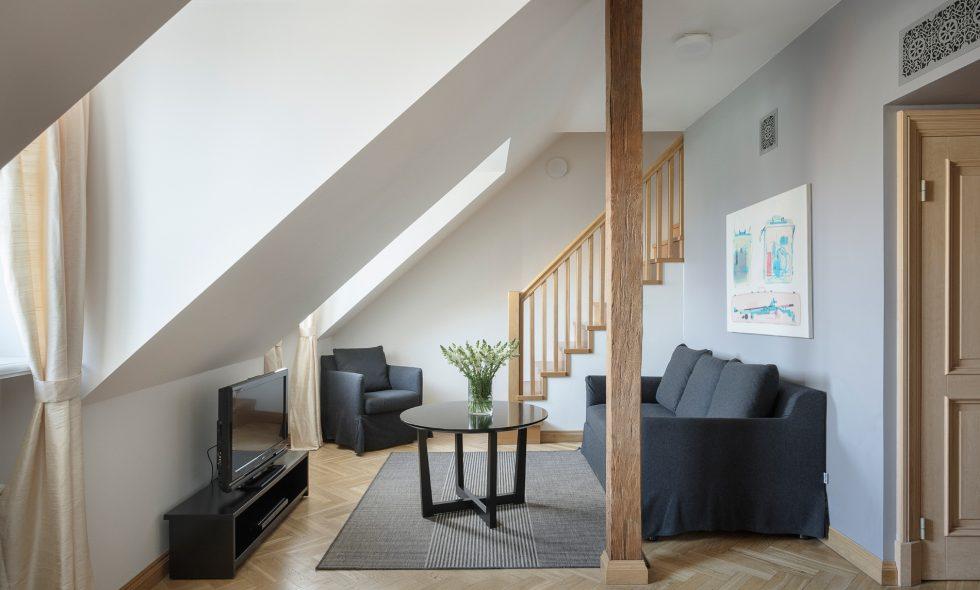 Divstāvu apartamenti — Pirmajā stāvā plaša dzīvojamā telpa ar koka sijām, atpūtas zonu, iebūvētu virtuvi un ēdamgaldu