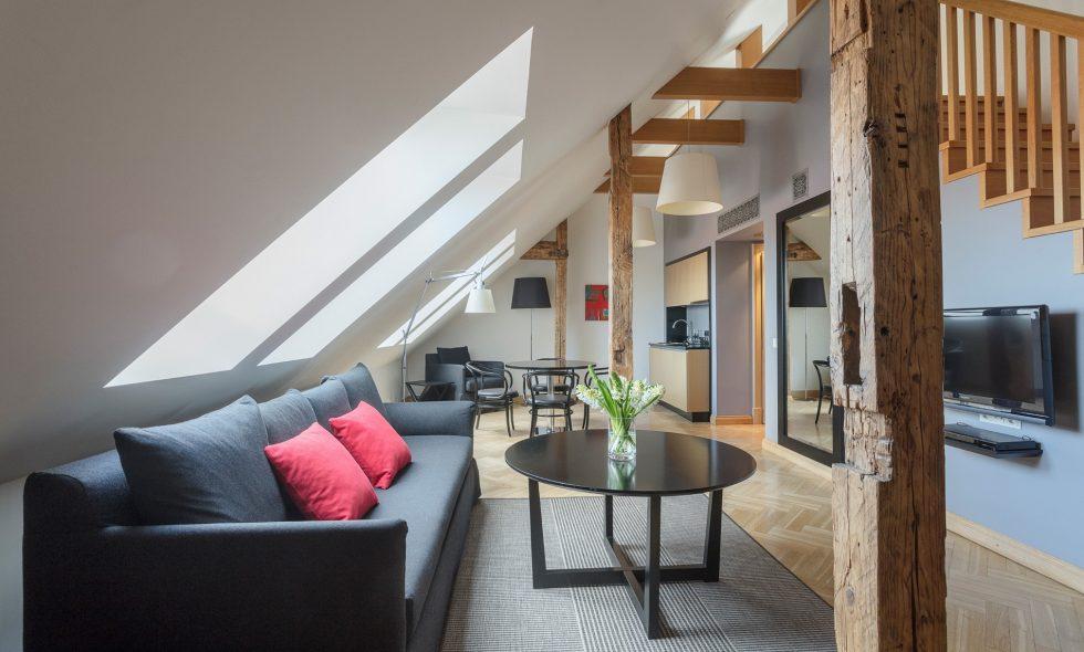 Dzīvojamā telpa pirmajā stāvā ar dekoratīvām koka sijām, atpūtas dīvāniem, ēdamgaldu un virtuvi