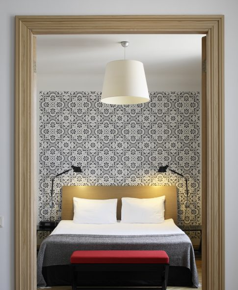 Senior Suites — Bedroom with a decorative mural, designer lamps, parquet floor and separate TV set