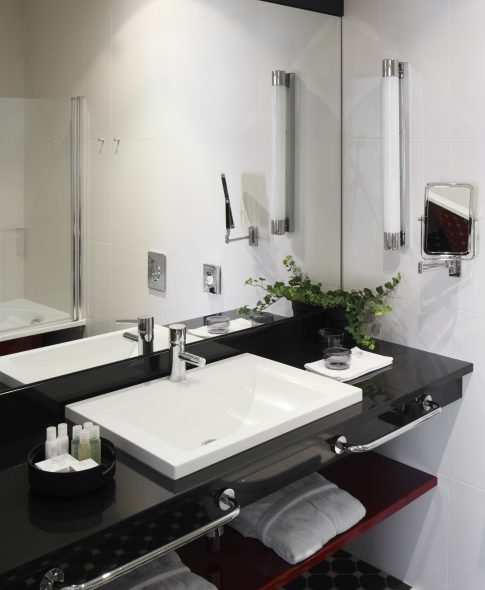 Studio Apartments — Roomy and comfortable bathroom with convenient shelves and makeup mirror. Bathrobes and slippers