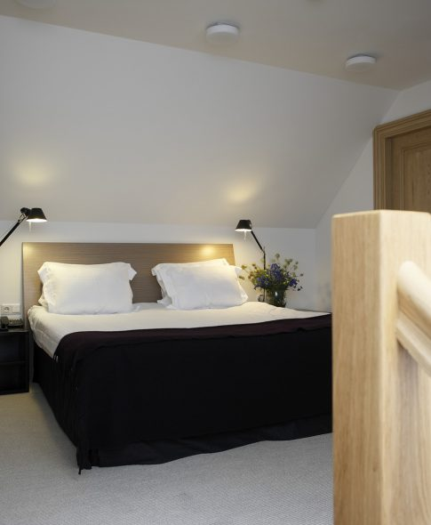 Two-Storey Suites — On the second floor, comfortable bedroom with spacious en-suite bathroom. Artemide designer lamps